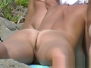 Three beach nudist girls tanning their tight bodies on the b
